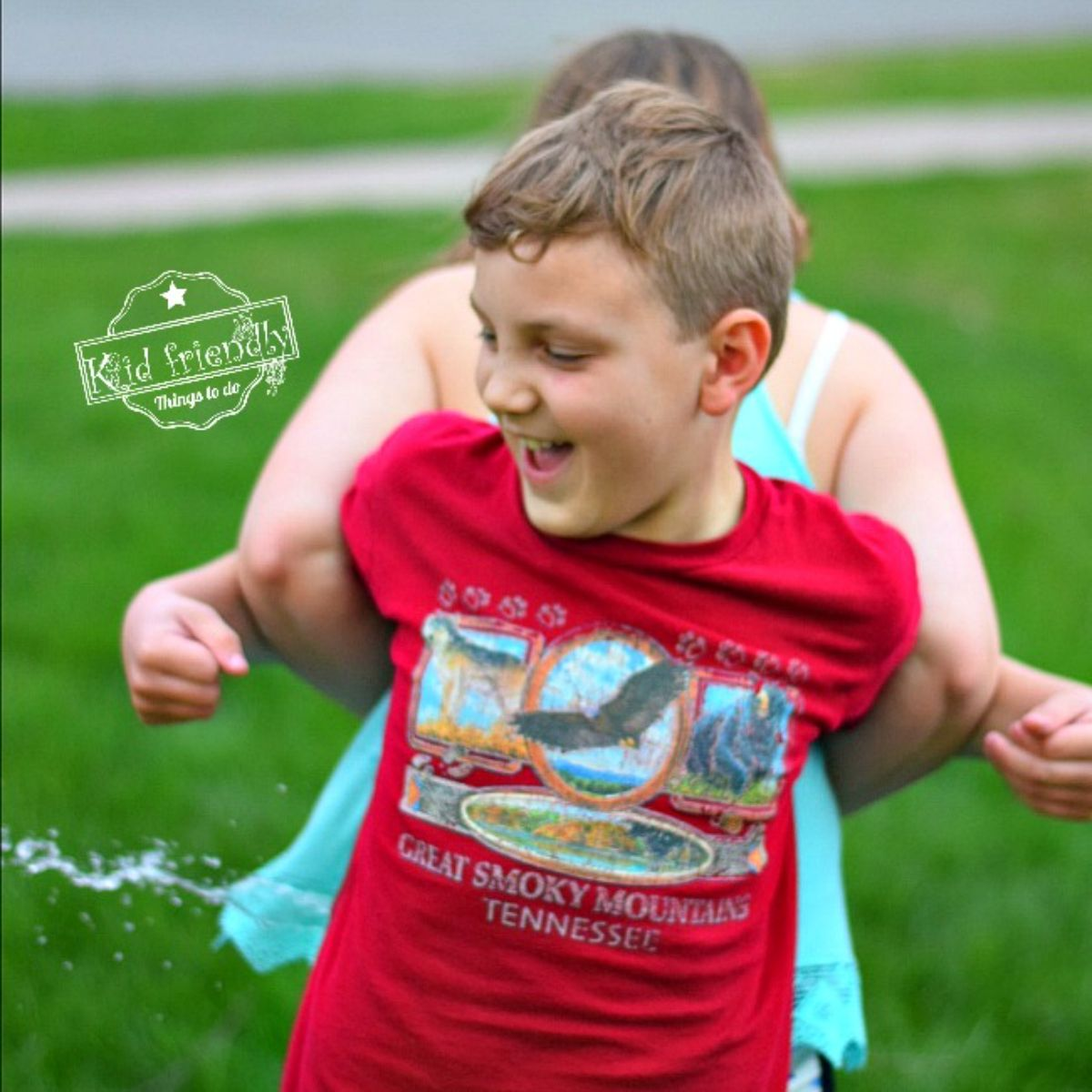 """the text reads """"Kid friendly things to do"""" the image is of a girl and boy linking arms whilst facing away from each other. A burst water balloon is between them"""