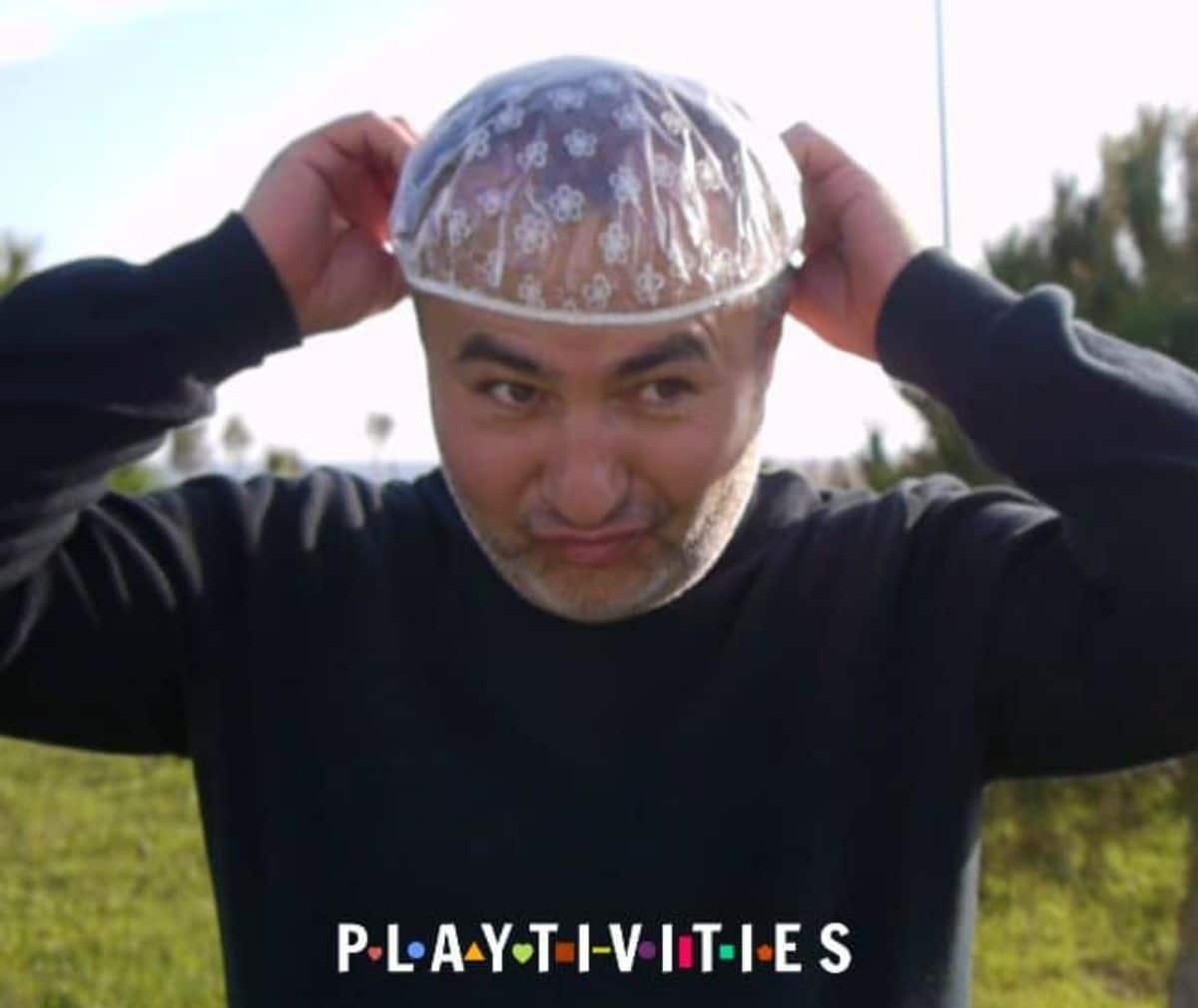 A man stands outside in a dark jumper and is putting a shower cap on his head.