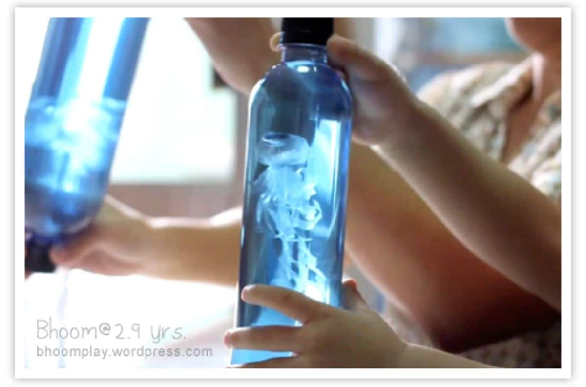You can see the hands of 2 children holding blue bottles filled with liquid and what looks like a jellyfish