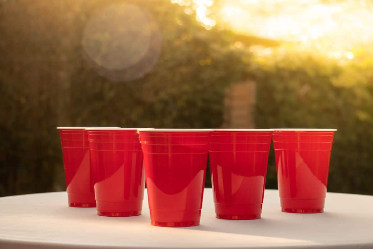 with green foliage in the background, 5 red solo cups sit on a white table