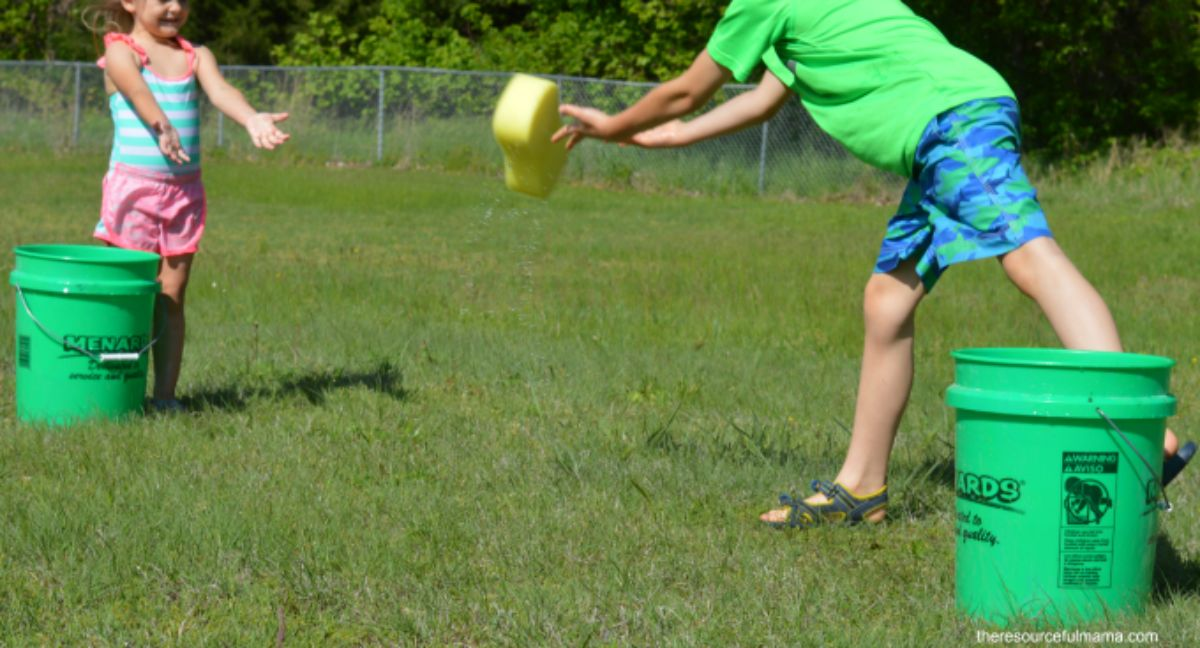 2 children stand in a garden with green buckets next to them. They are throwing a yellow sponge betweem them