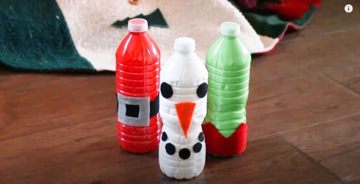 on a table are 3 watr bottles painted as a snowman, elf and father chirstmas