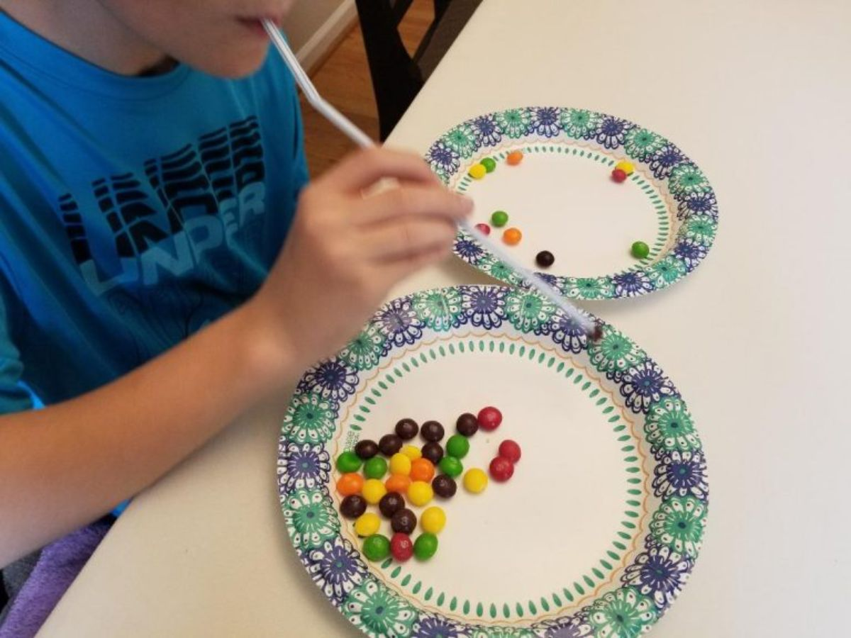 on a white table are 2 patterned plates with skittles on them. A child in a blue shirt is moving skittles between the paltes with a plastic straw