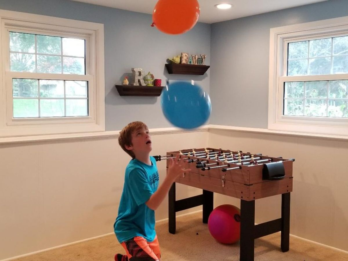 in a room in front of a table football table is a small boy. He is keeping a blue and red balloon up in the air