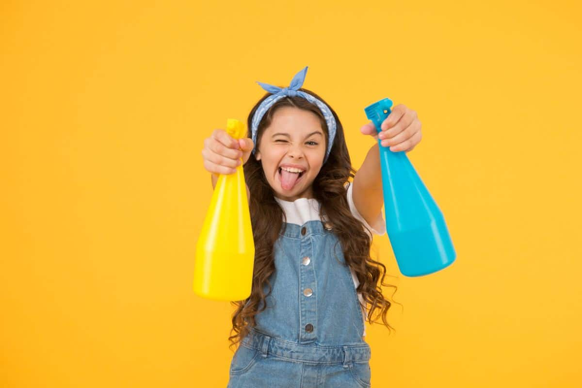 on a yellow background a girl in dungarees and a hairband is sticking out her tongue and pointing one blue and one yellow spray bottle at the camera