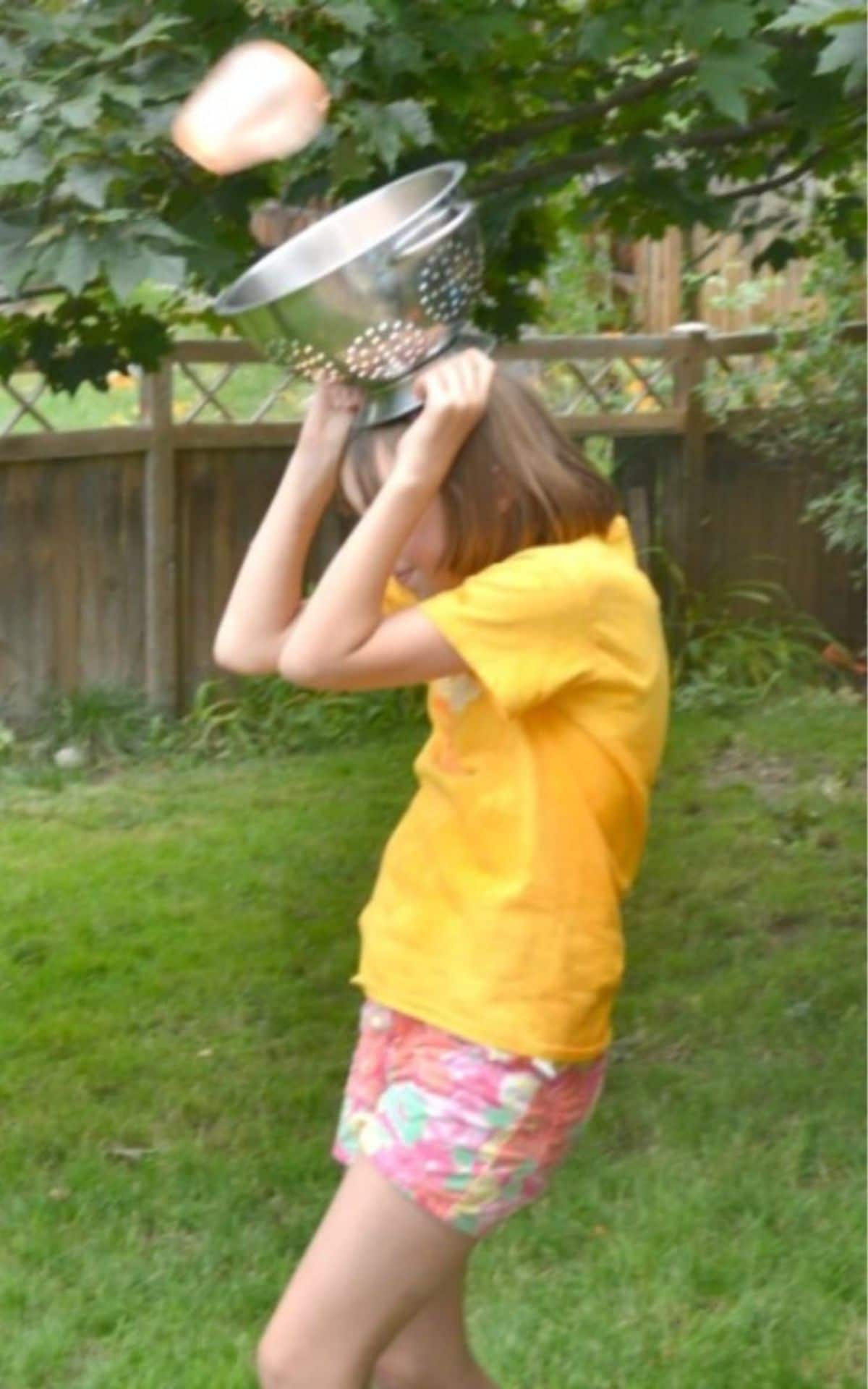 a girl in a yellow shirt and shorts is in a garden with a colander on her head. A sponge is heading into the colander