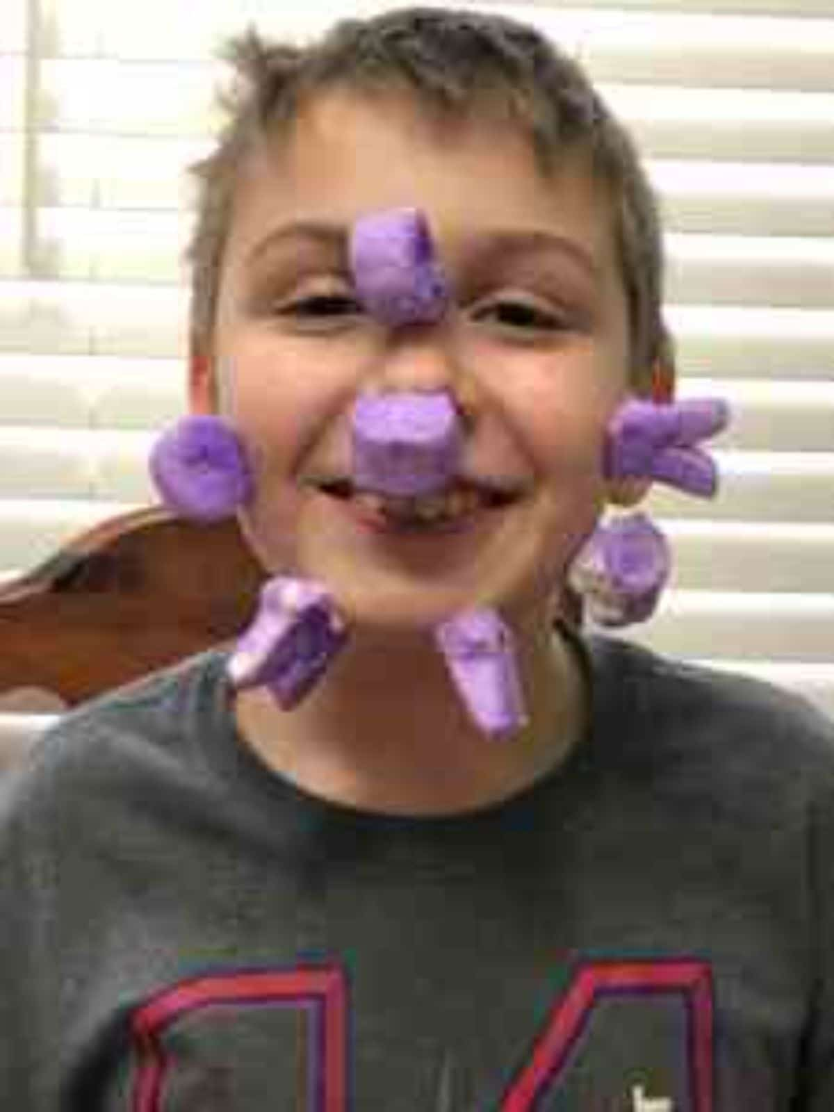 a boy in a grey tshirt smiles at the camera. He has 7 purple marshmallow peeps stuck to his face.
