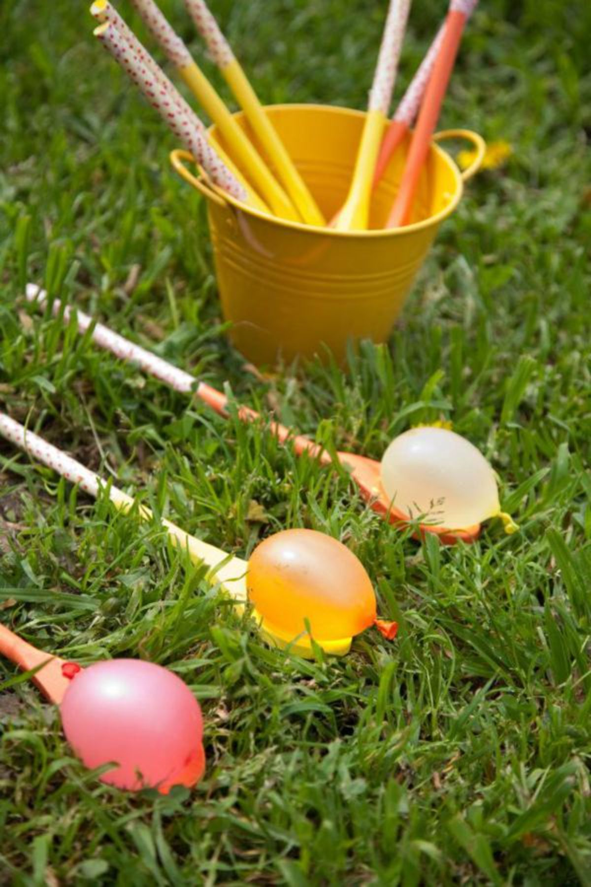 a yellow bucket with wooden spoons sticking out of it sits on grass, with 3 wooden spoons in front of it holding water balloons on them