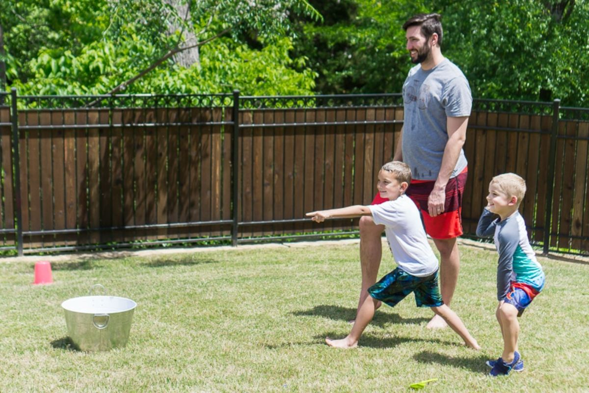 2 boys and a man stand in a garden in front of a dark fence. One boy is throwing a wet sponge into a metal bucket