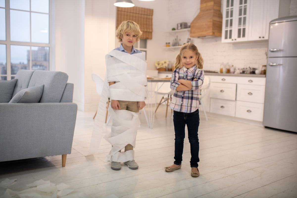 in a white kitchen next to a sofa are a boy and a girl. The boy is wrapped in toilet paper. The girl is smiling. Both children are smiling facing the camera
