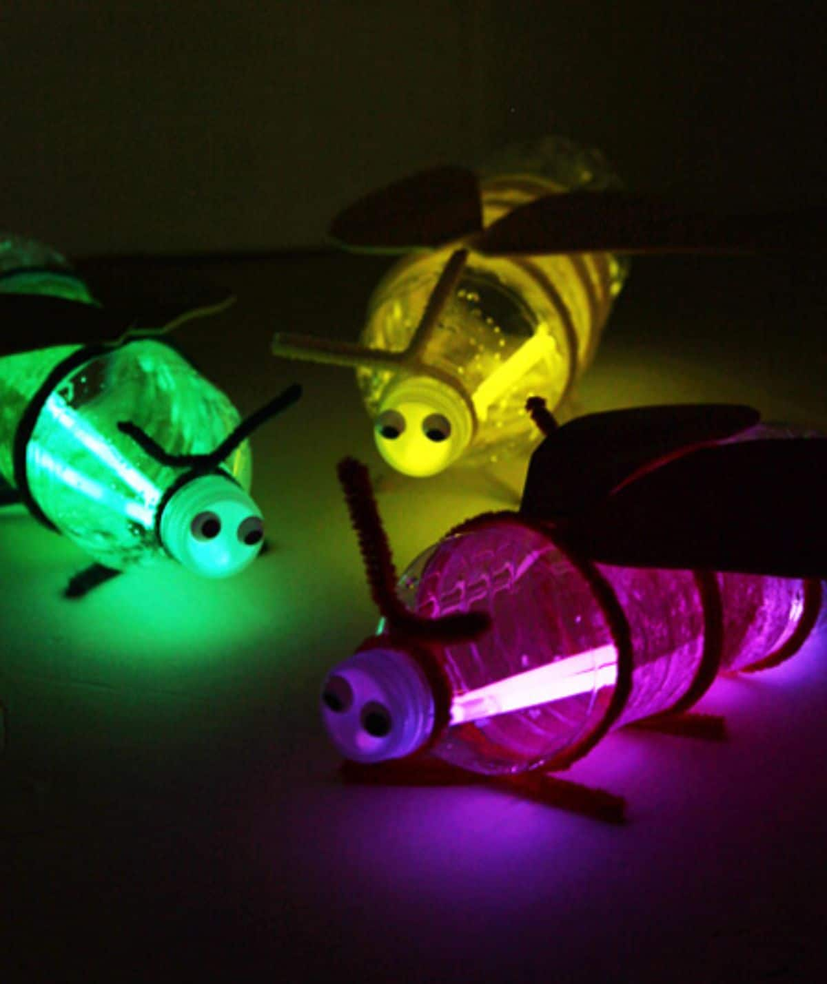 3 bottles are filled with purple, green and yello glowsticks are decorated to look like fireflies