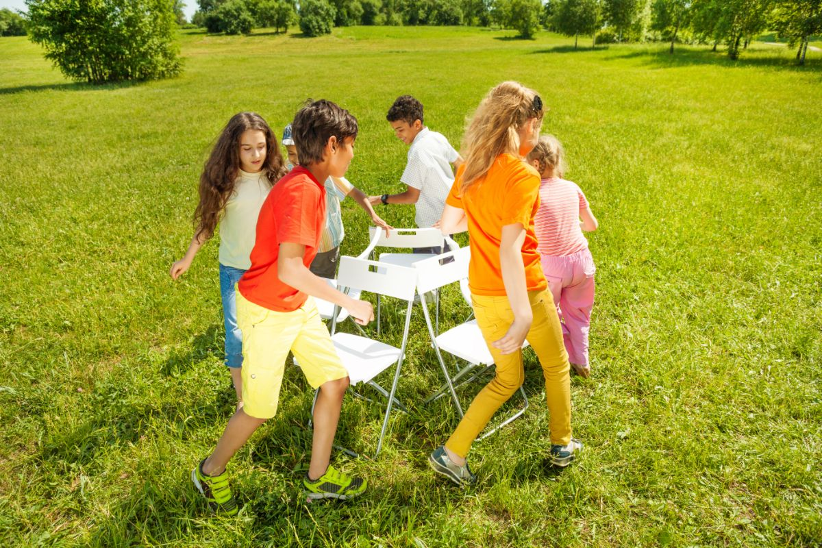 6 children in a garden are walking around a group of 4 white chairs