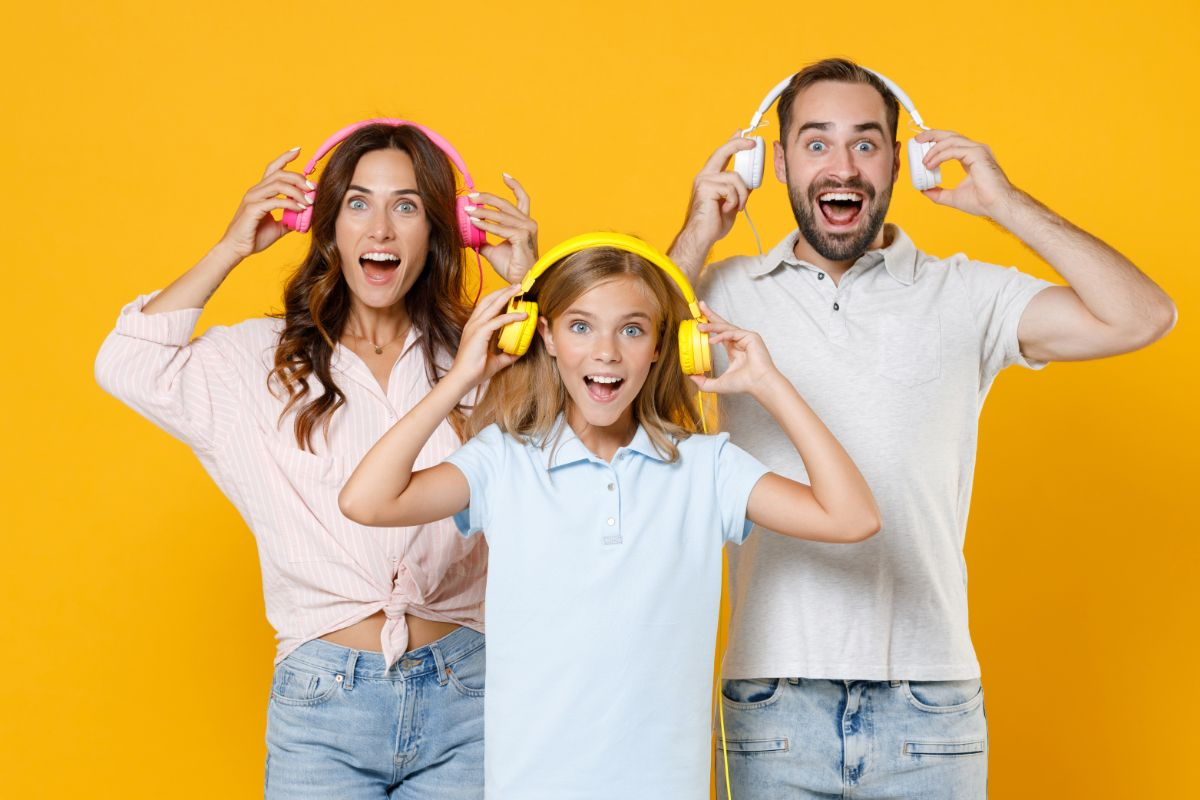 a man, woman and girl stand in front of a yellow background. They are all wearing headphones that they are holding away from their ears, and they are smiling.