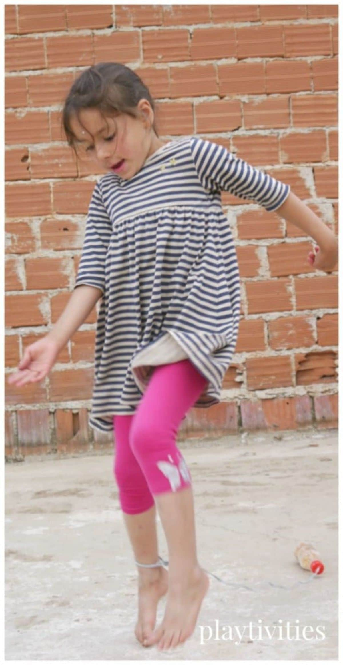 A girl in a striped top and pink leggings is standing in a yard in front of a brick wall. She has a string tied around her waist with a plastic bottle on the end of it