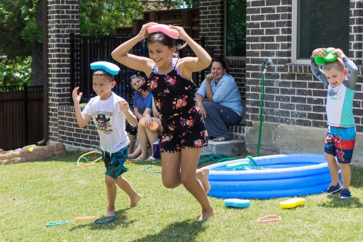 a girl and 2 boys run across the garden holding sponges on their heads. Behind them is a blue paddling pool. 2 women look on, smiling.