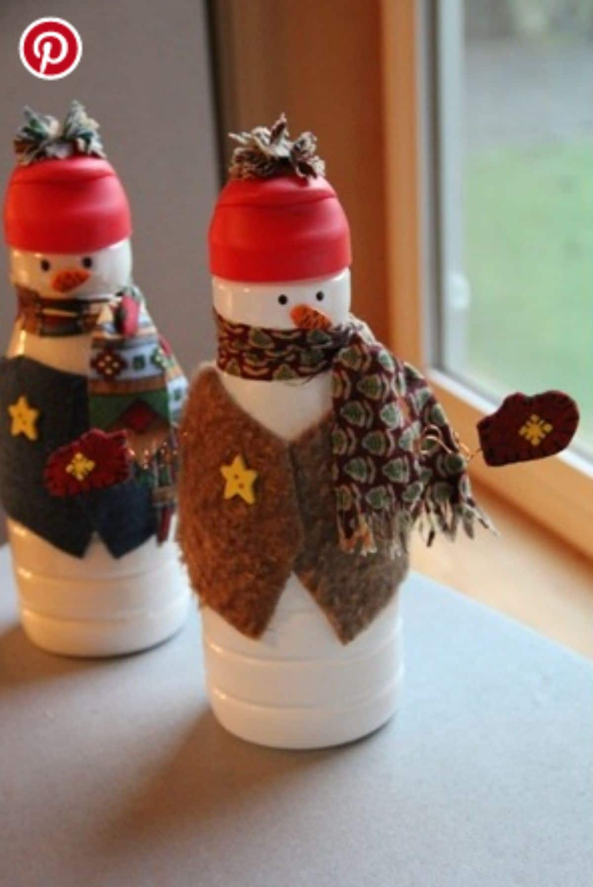 in front of a window are two creamer bottles decorated in material to look like snowmen