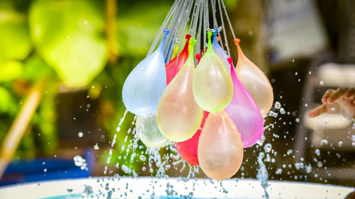 a close up shot of a group of water balloons hanging from filling tubes