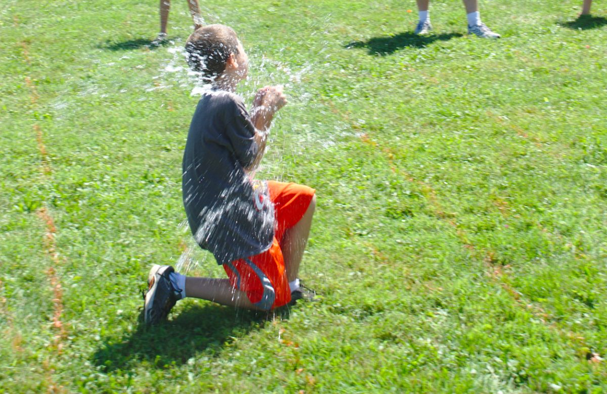 a boy in red shorts and a gray shirt kneels in a garden catching a water balloon that has burst all over him