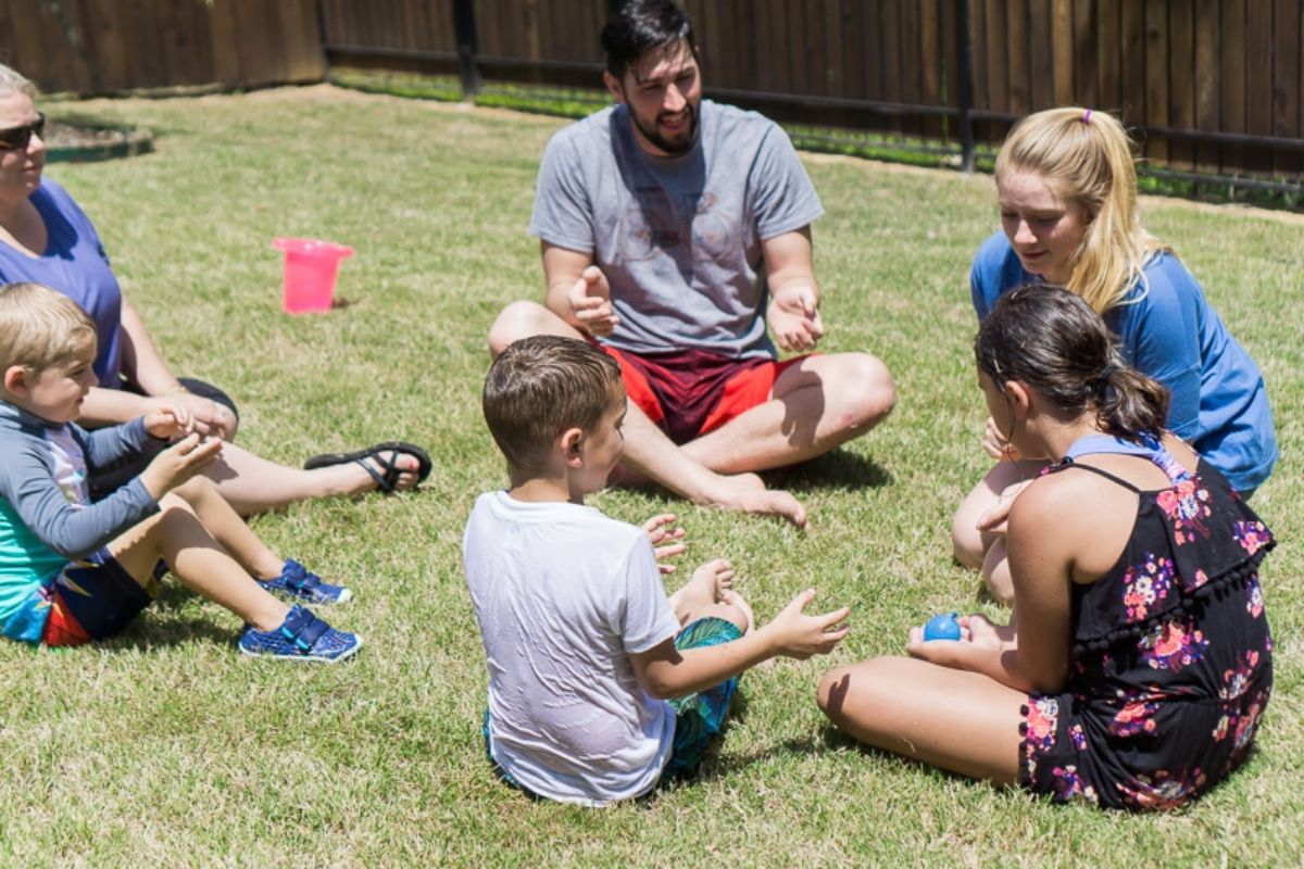 3 children, 2 women and one man are sat in a garden passing a water balloon between them