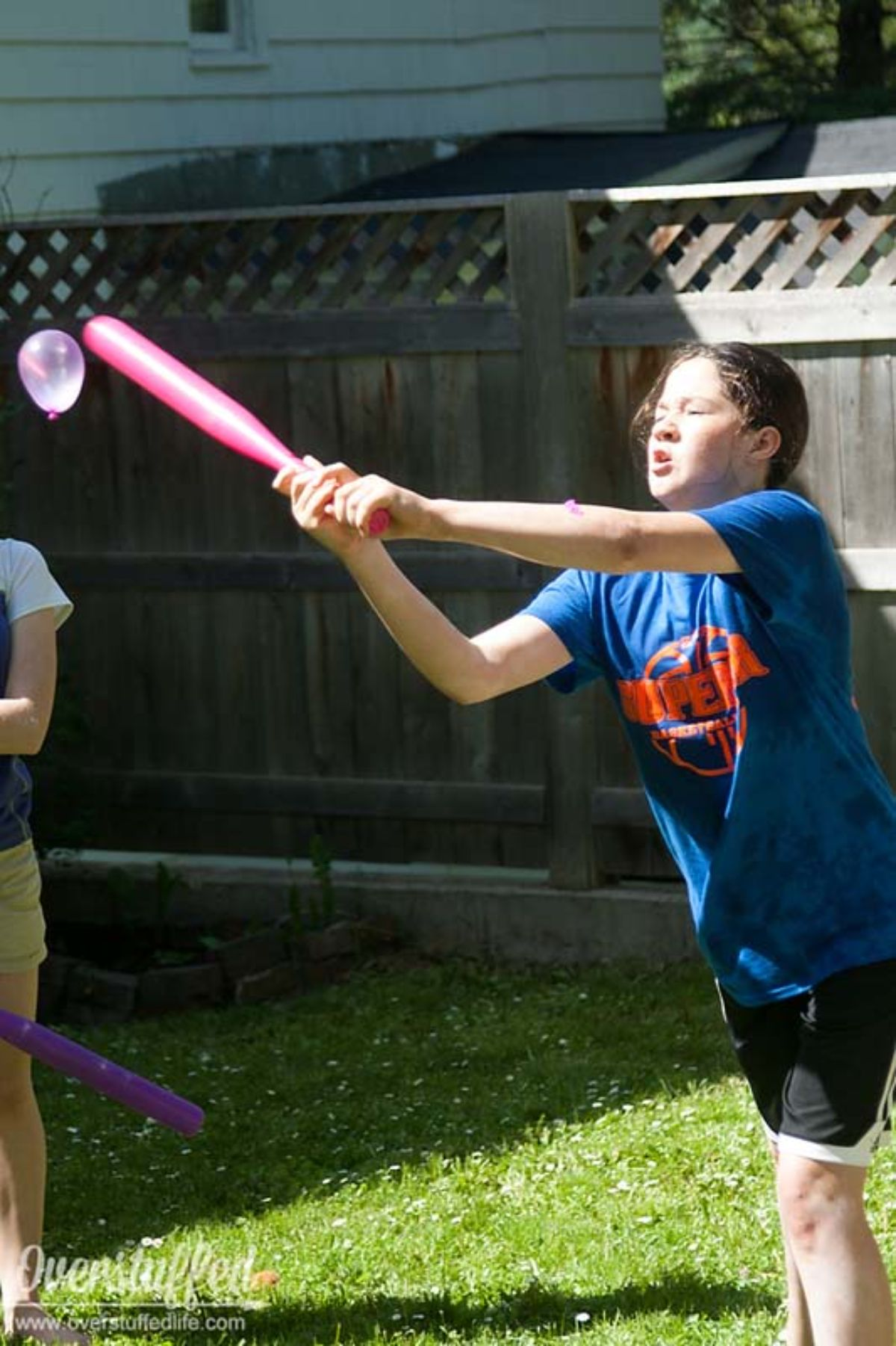 a girl in a blue shirt and shorts is hitting a water balloon with a pink bat in a garden