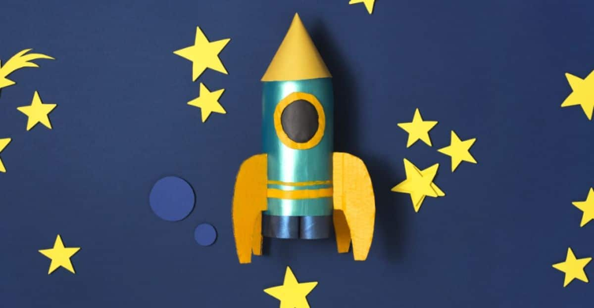 against a background of dark bue sky and yellow stars is a blue and yellow rocket ship made out of a plastic bottle