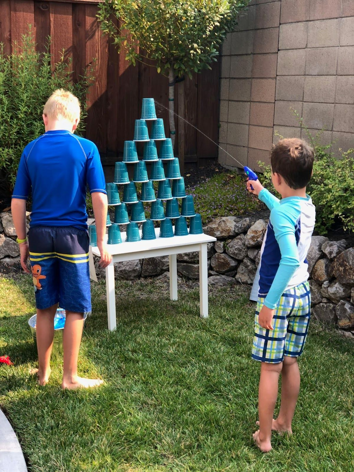 2 boys are standing in a garden in front of a white table on which a pyramid of blue cups is stacked. On eboy is pointing a blue water pistol at the pyramid