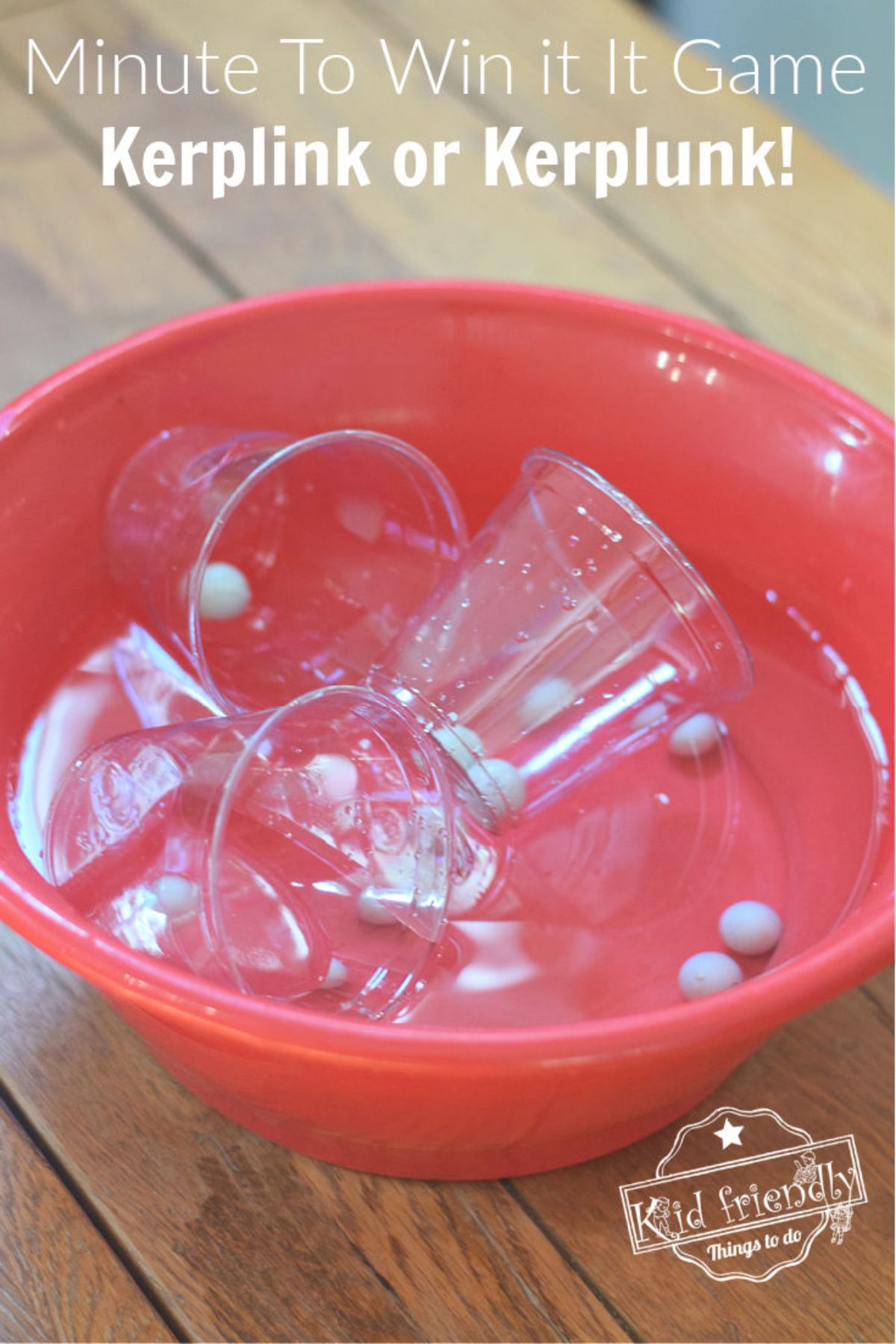 """the text reads """"Minute to win it game kerplink or kerplunk!"""". The image is of a red bowl on a wooden table. 3 clear plastic cups are in teh bowl, floating in water. Several marbles are in the bottom of the bowl"""