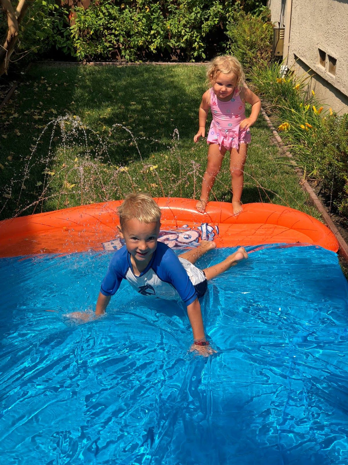 in a turfed garden a boy and a girl in swimwear are playing on a slip and slide