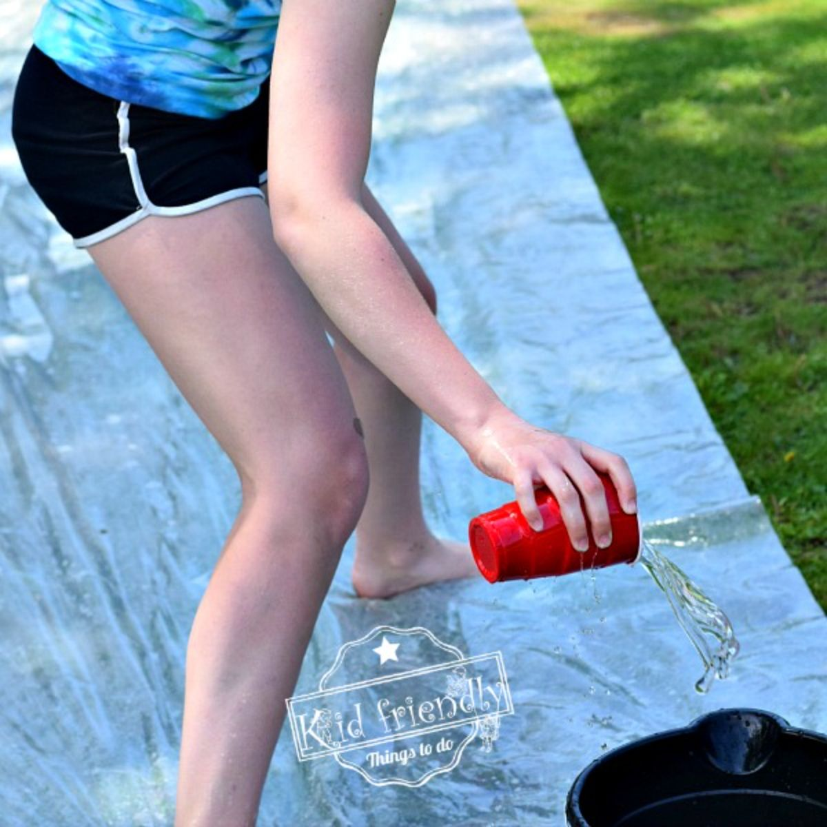 a partial shot of a child in shorts pouring water form a solo cup into a black bucket
