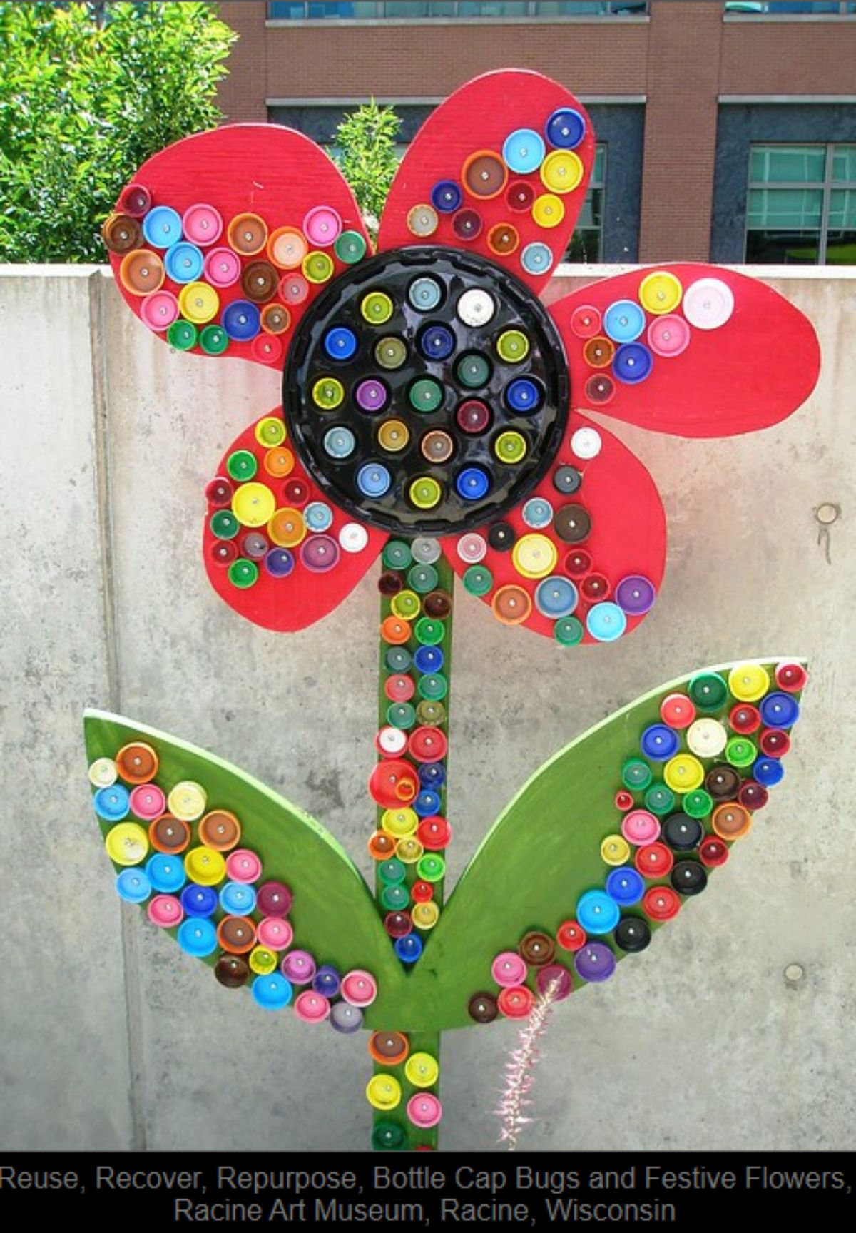 in front of a concrete wall is a flower made of wood and painted red and green. It is decorated with colored bottle tops