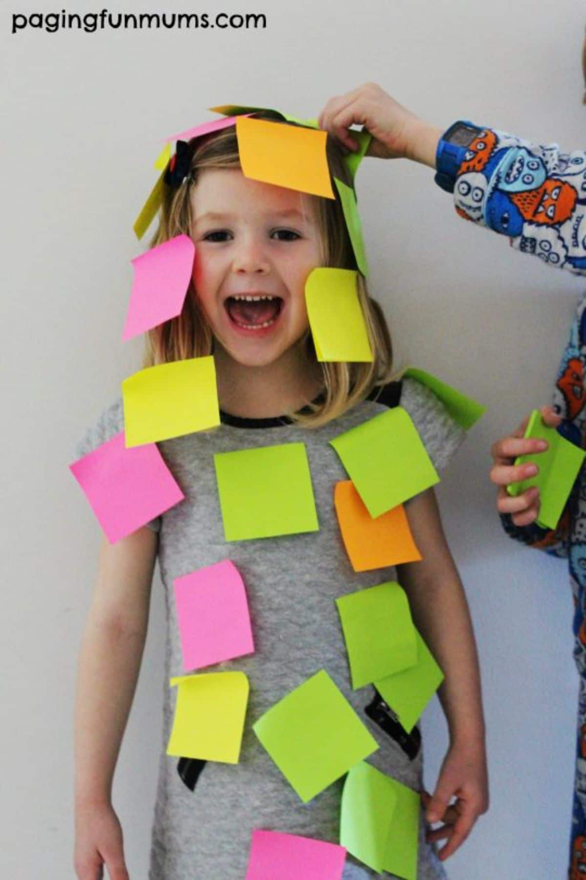 a girl wearing a grey dress is covered in coored post it notes. A hand apperared from the right hand side of the frame placing another post it note on her head