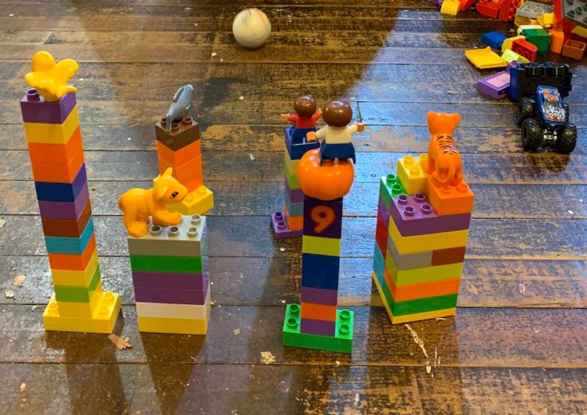 on a wooden floor are several towers made of duplo. a ping pong ball is rolling toward them