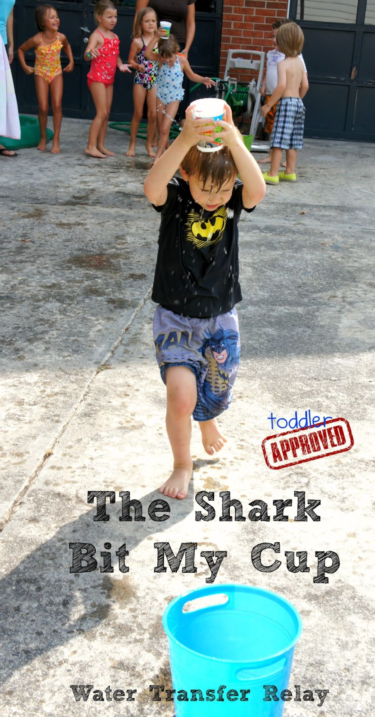 """The text reads """"The shark bit my cup. Water transfer relay"""" The image is of a boy in a black shirt and shorts holding a cup over his head. There is a group of children standing in the back of the shot"""