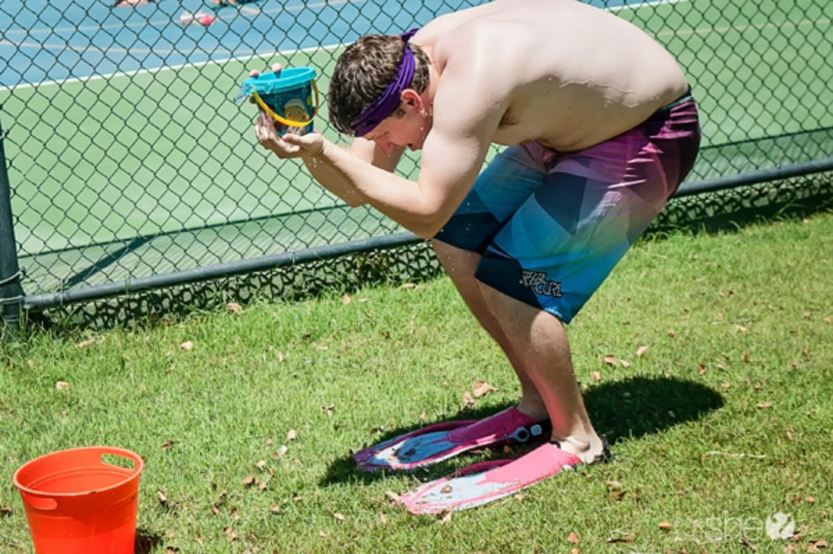 A man crouches down whilst wearing flippers, swimshorts a and a headband. He is holding a buscket in front of him