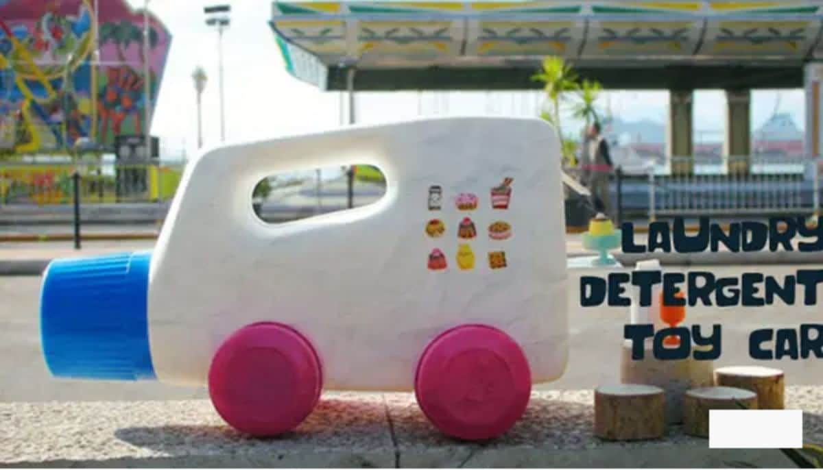 on a wall is a laundry detergent bottle with pink bottle cap wheels attached, making it look like car