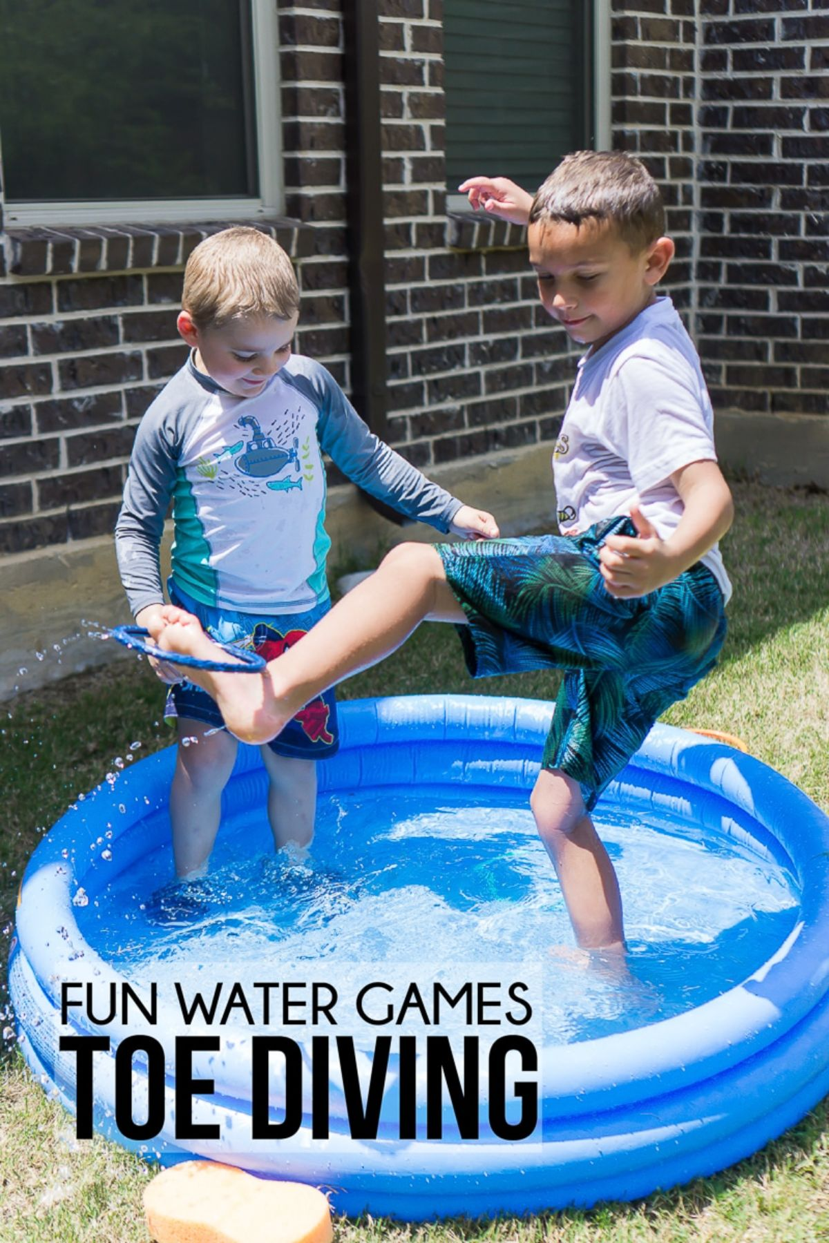 2 boys are in a small blue paddling pool filled with water. One boy has lifted his left foot up and is balancing a blue ring on it