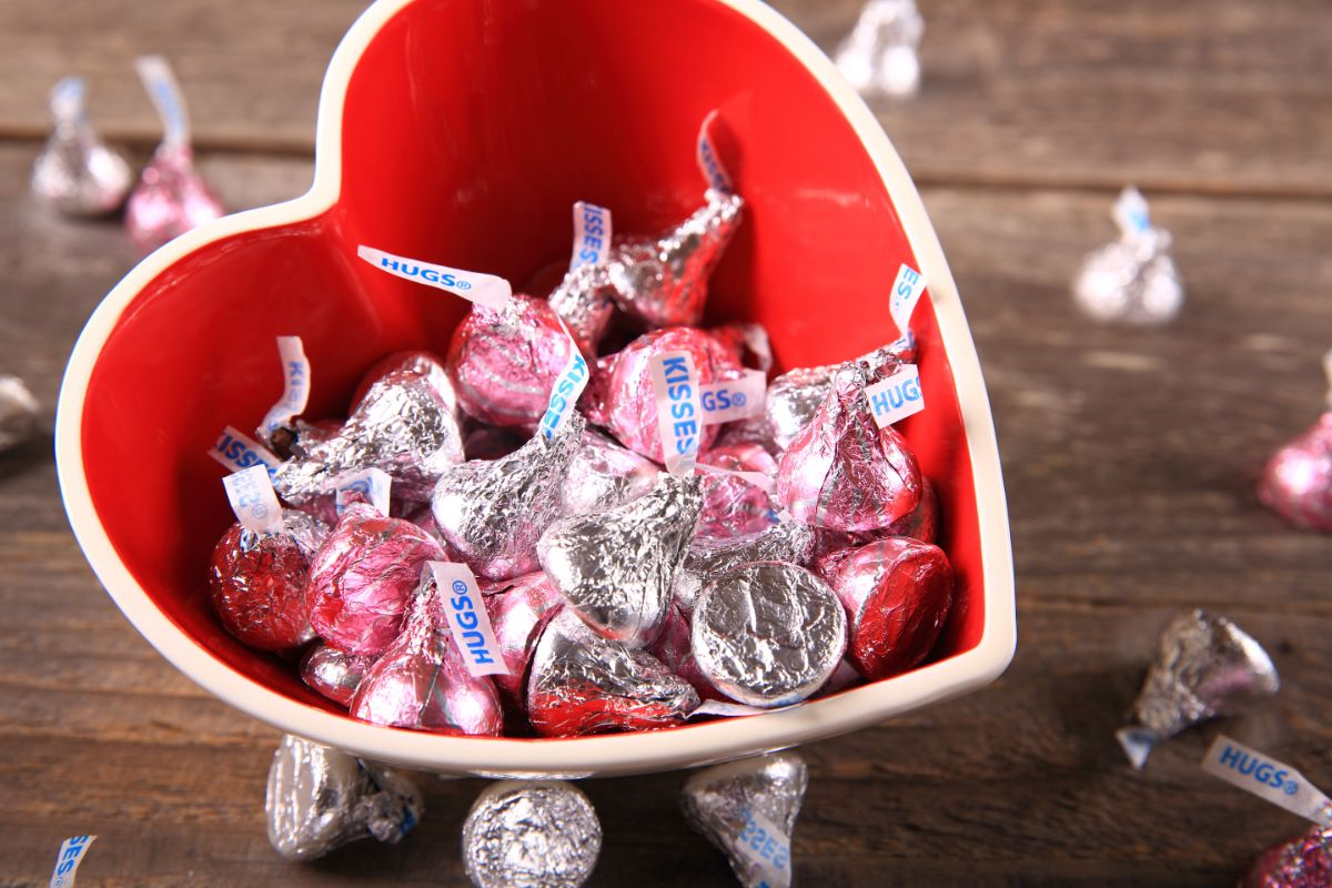 a wooden table with a heart-shaped ceramic bowl with a red inside and a white rim. The bowl is filled with hershey's kisses. More kisses are scattered around the bowl