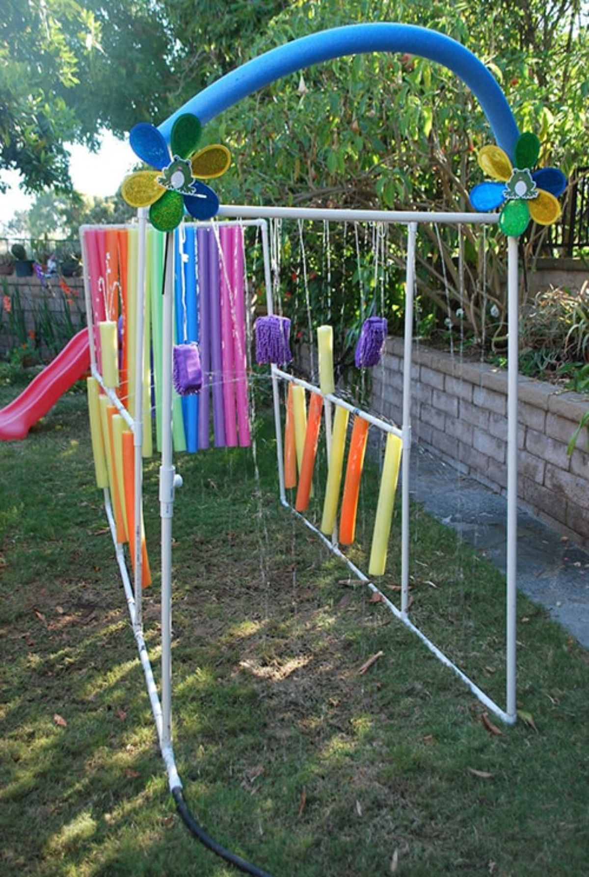 Standing on grass is a white tubular structure with pool boodles hanging from it like a car wash