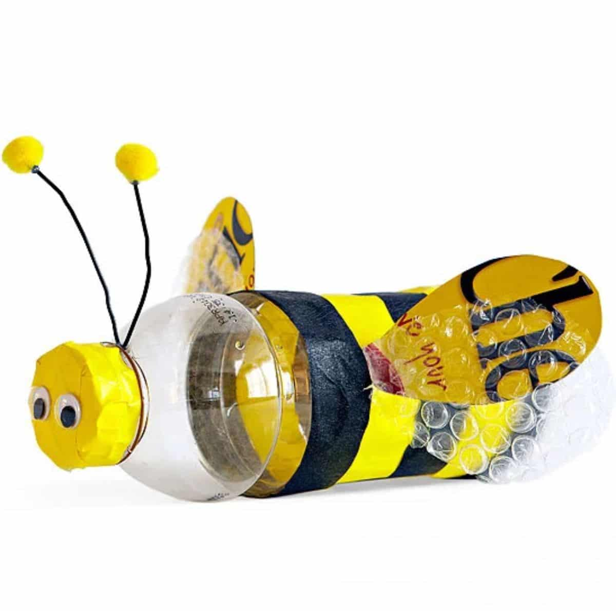 a water bottle is decorated with black and yellow tissue paper to look like a bumble bee.