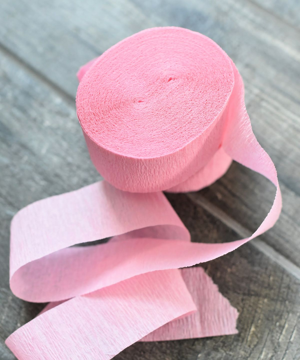on a grey background is a roll of pink tissue paper, unravelling