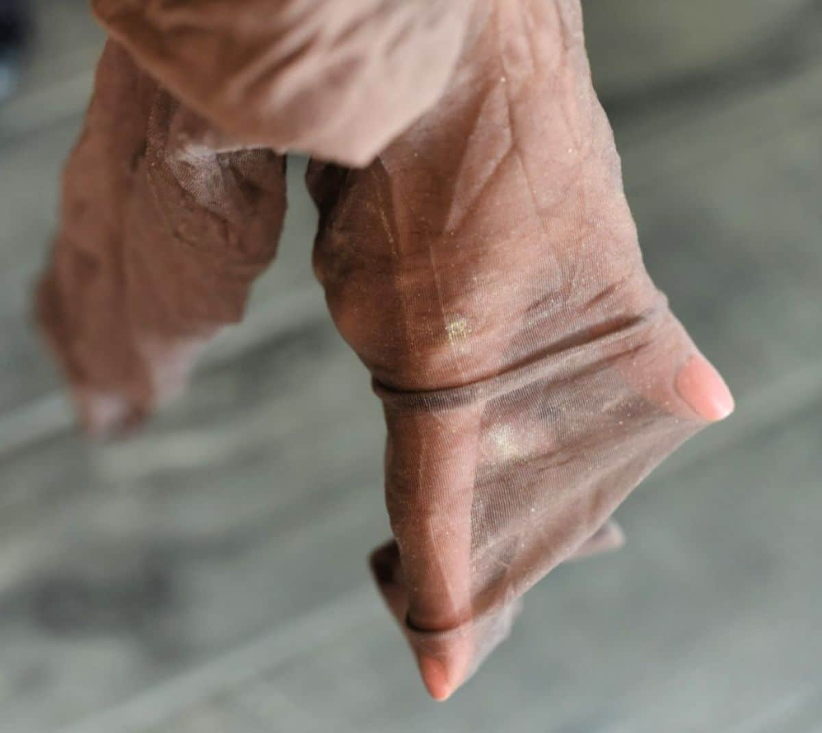 a hand is pushing to the bottom of a leg of pantyhose