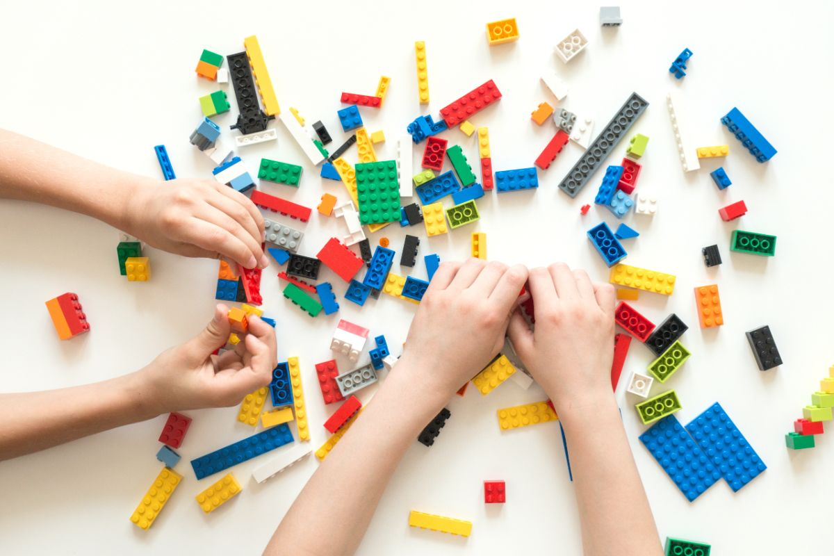 a white table with lego blocks scattered over it. two children's arms play with the lego