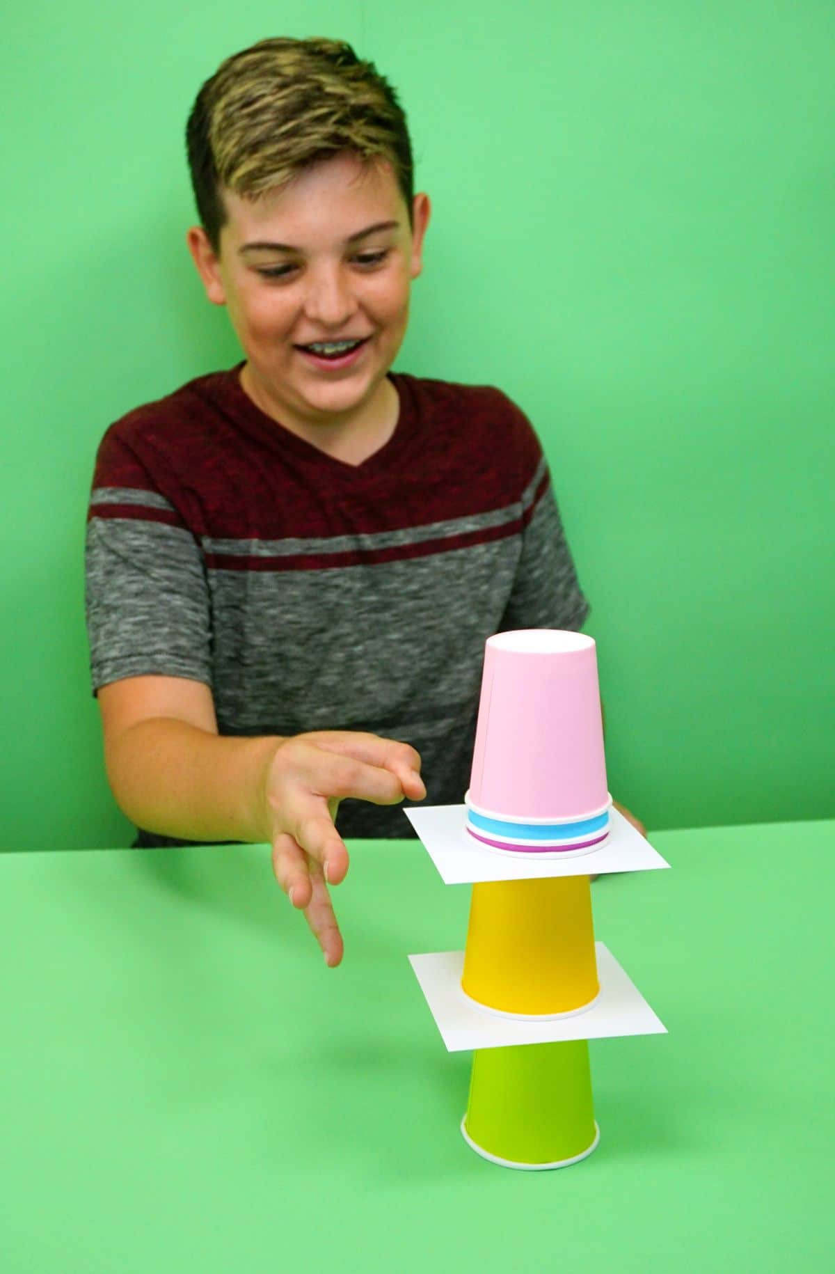on a green background with a green table a boy sits down. He s reaching toward a tower of 3 paper cups with white squares of cardboard inbetween them