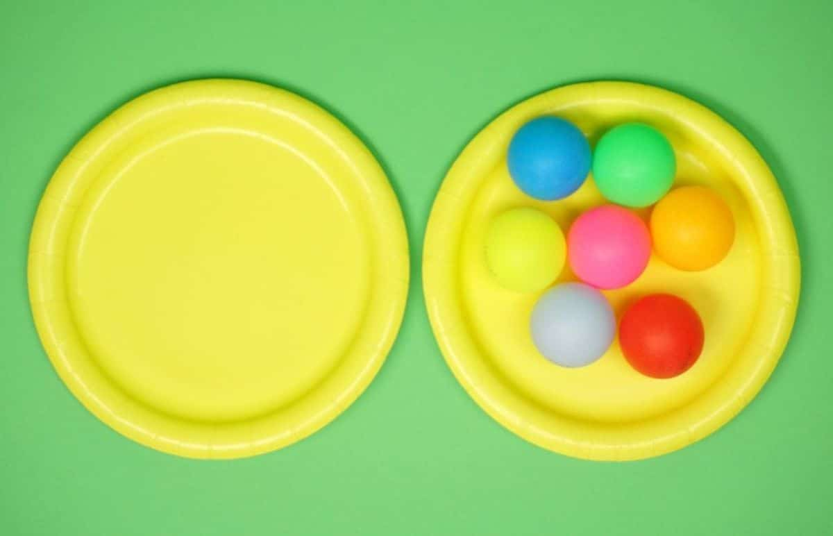 on a green background are two yellow plates. On the right hand yellow plate are 7 colored ping pong balls