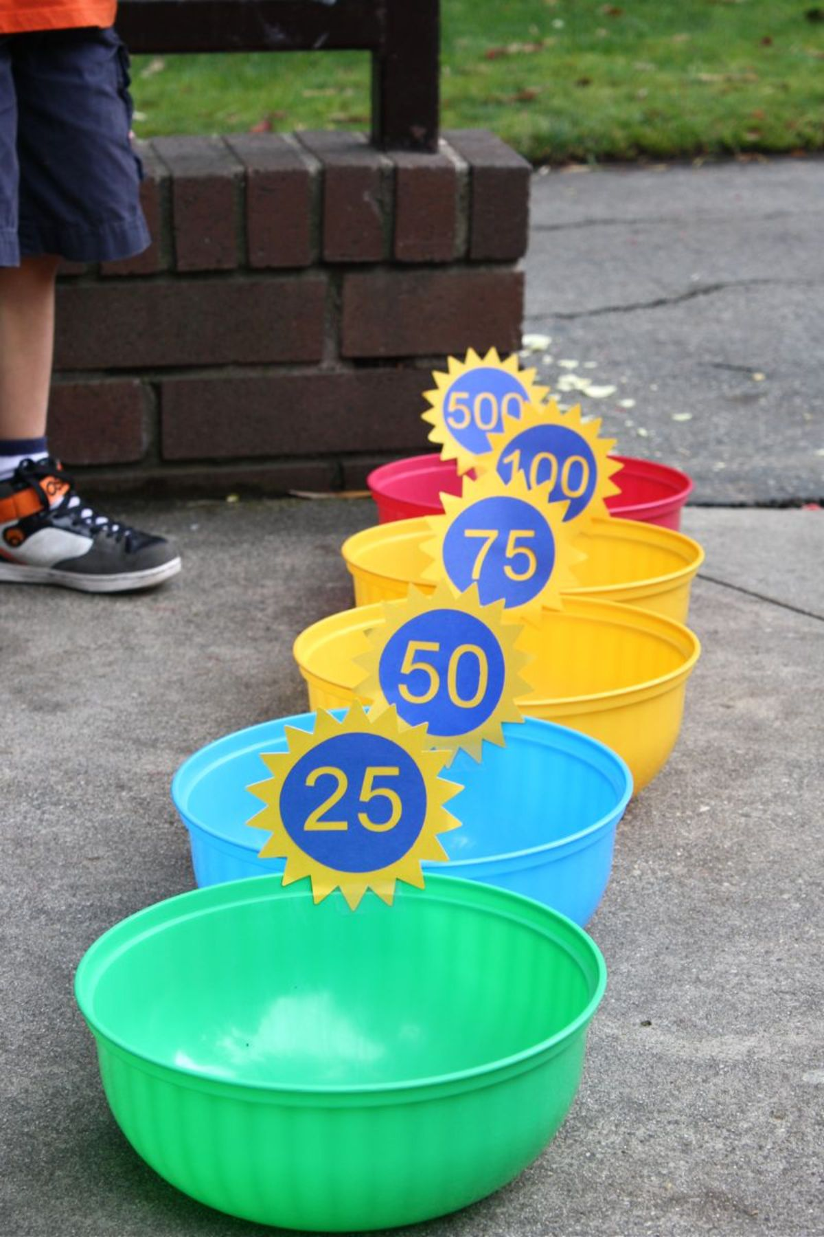 on a patio multi-colored plastic bowls are in a line. They are numbered 25, 50, 75, 100, and 500. You can see a boy's feet in the background