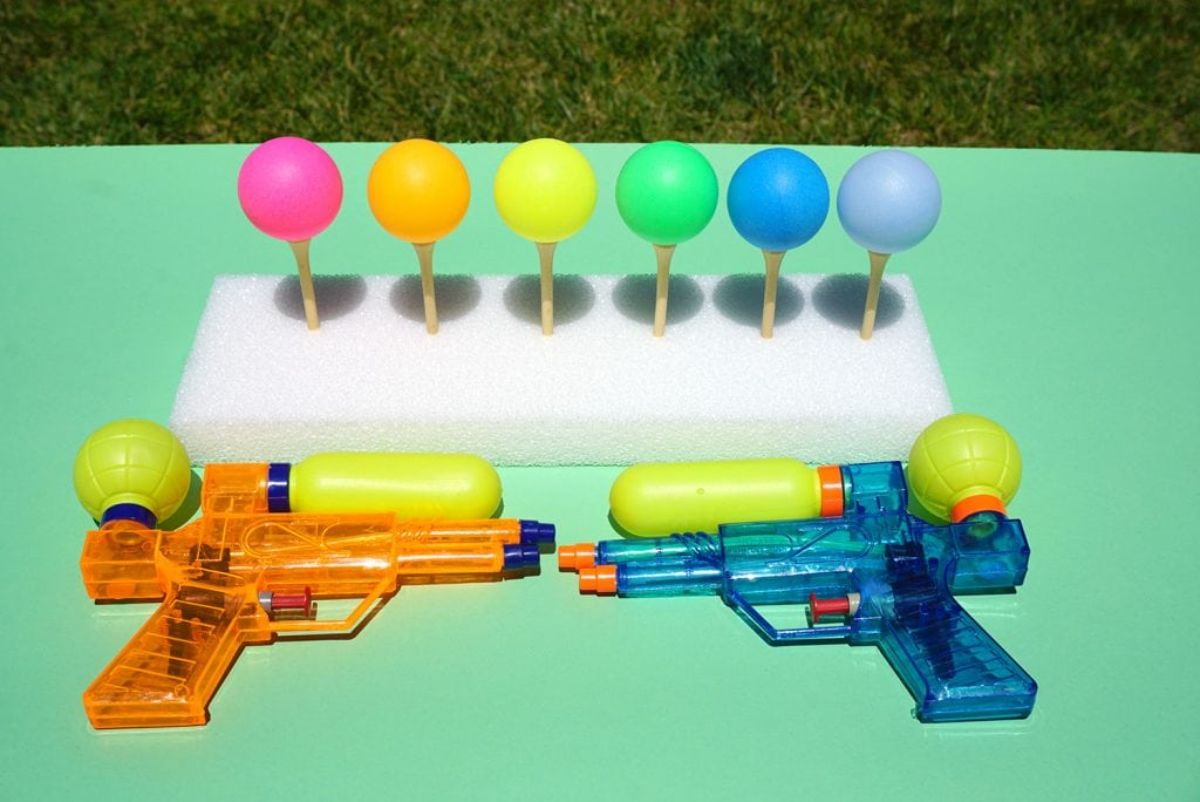 on a green table are an orange water gun and a blue water gun. Behind these is a polystyrene rectangle. Stuck into this are 6 golf tees with colored ping pong balls on top of them