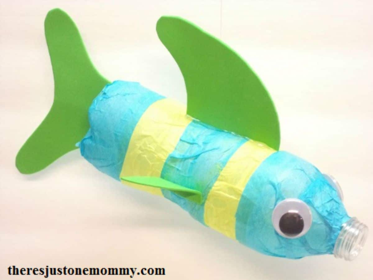 a plastic water bottle wrapped in blue and yello tissue paper, googly eyes are stuck on the front and fins and a tail are stuck on in green card