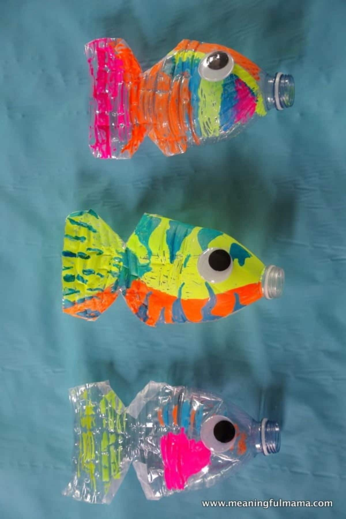 against a blue background are 3 crushed water bottles made up like fish with paint and googly eyes