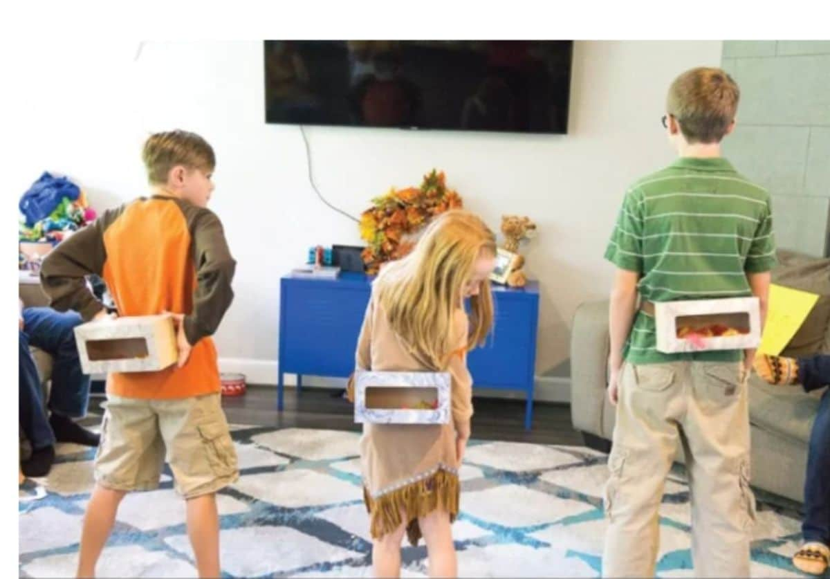 3 children stand in a living room. Tied to their backs are tissue boxes with ping pong balls inside them