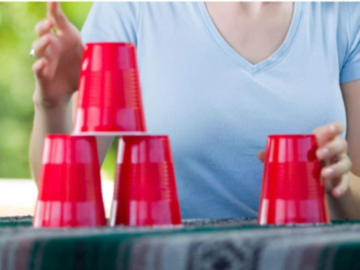 a woman in a blue shirt sits behind an outdoor table. She is stacking 4 red solo cups on the table.